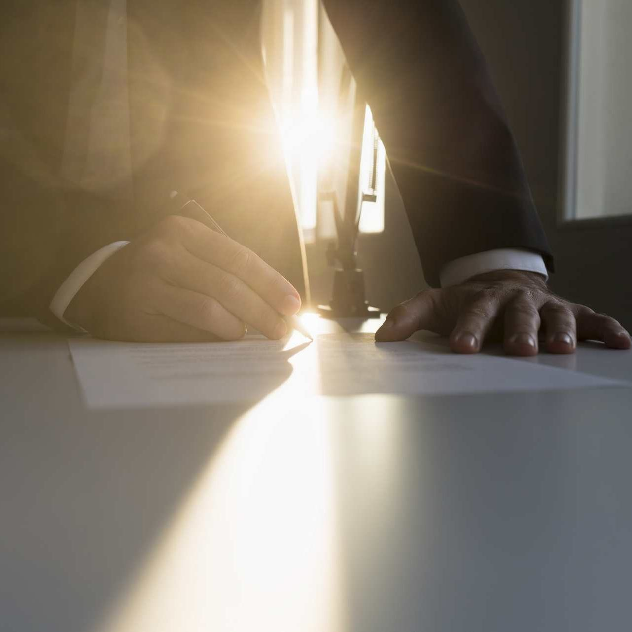 Close-up of the hands of a businessman wearing formal suit while signing an important agreement at desk in the office at sunset.
